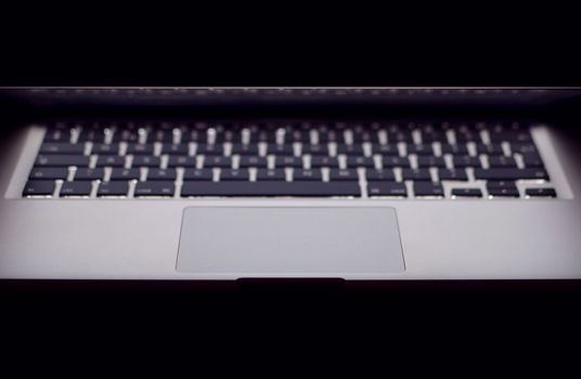 laptop half-closed against a dark background
