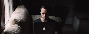 Main in dark room on laptop