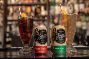 sailor jerry spiced rum and cola cans in front of two classes and a liquor case, one of the new cocktails available at BWS