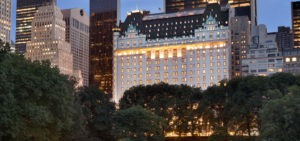 the plaza hotel at night lit up through green trees one of the most well-known US landmarks